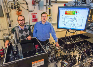 """Giacomo Coslovich (left) and Robert Kaindl (right) next to the laser setup that generates extremely short pulses of light at """"mid-infrared"""" wavelengths, far beyond the spectrum perceptible by the human eye."""